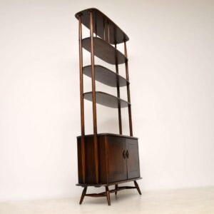 A stunning and rare bookcase cabinet by Ercol in solid Elm, this dates from around the 1960's. It's in really good original condition, with some minor wear and a few minor marks here and there. Overall this is clean, sturdy and sound, the back is also nicely finished so this can be used against a wall or as a free standing room divider. As with all Ercol products, the quality of construction is really high, and this displays stunning Elm grain patterns throughout. The middle two shelves are adjustable and removable, they can be placed at any height along the frame between the second from top shelf and the cabinet. Width - 92 cm Depth - 41 cm Height - 191 cm